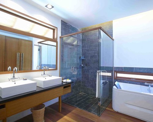 A bathroom with shower stall bathtub and double sink vanity.