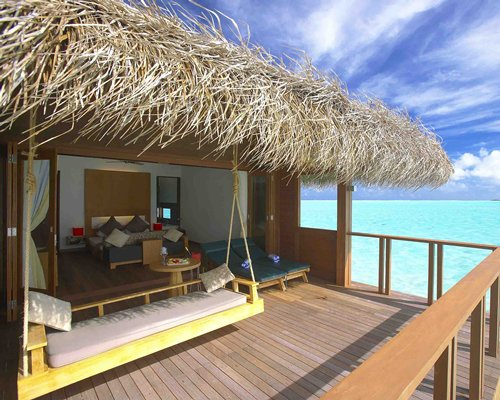 A well furnished bedroom and a balcony with chaise lounge chairs and wooden swing alongside the beach.