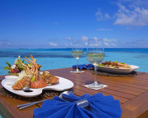 Outdoor dining with food items and beverage on the table alongside the ocean.