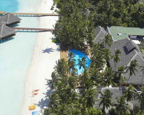 An aerial view of the resort property surrounded by trees alongside the beach.