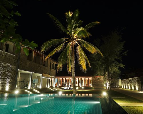 An outdoor swimming pool alongside resort units at night.