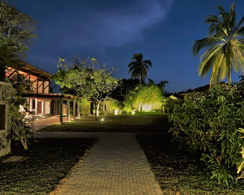 A well maintained lawn alongside trees plants and resort units at night.