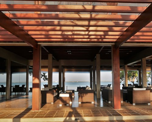 A well furnished indoor lounge area with a view of the water.