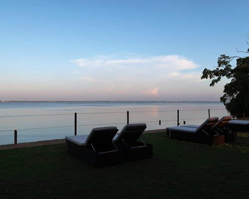 View of the water alongside chaise lounge chairs.