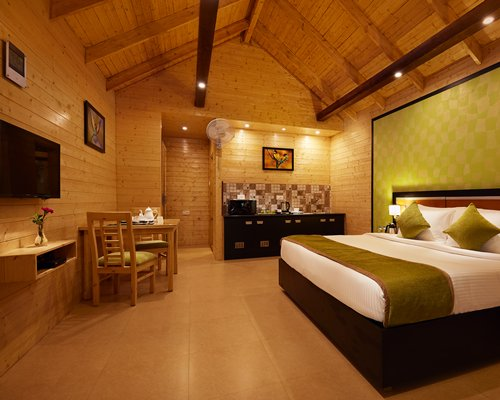 A well furnished bedroom with a double bed television and an oven.