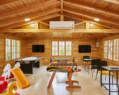 An indoor recreational room with kid's playscape area and television.