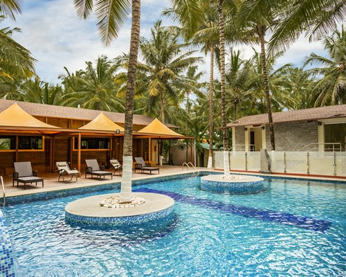 An outdoor pool with chaise lounge chairs sunshades and coconut trees alongside the resort unit.