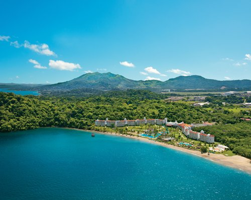 Aerial view of resort with ocean and mountains.