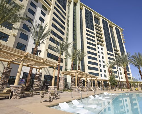 Exterior view of The Berkley Las Vegas with an outdoor swimming pool chaise lounge chairs and palm trees.