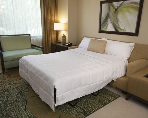 A well furnished bedroom with a queen bed and a sofa.
