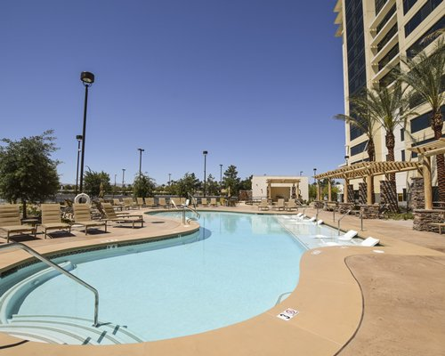 An outdoor swimming pool with chaise lounge chairs alongside a multi story resort unit.