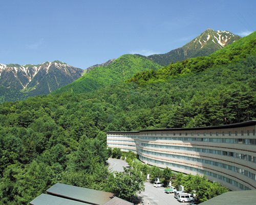 An exterior view of the Hotel Ambient Azumino with parking surrounded by wooded area.