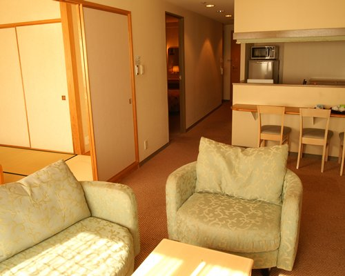 A well furnished living room and an open plan kitchen with breakfast bar.
