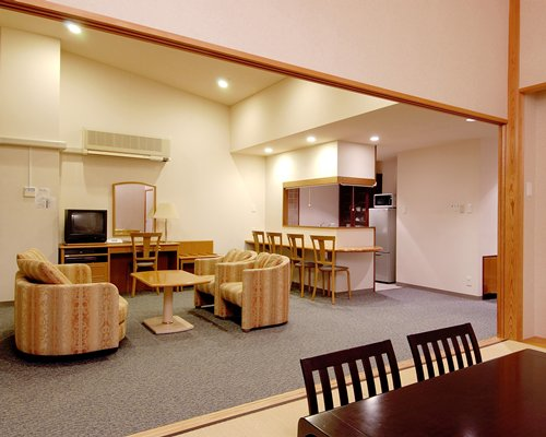 A well furnished living room with a television dining area and an open plan kitchen with breakfast bar.