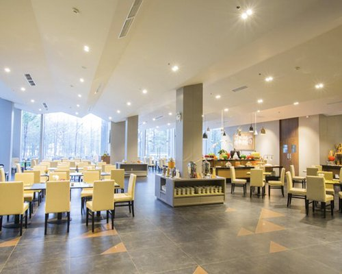 A large indoor fine dining area at the resort with an outside view.