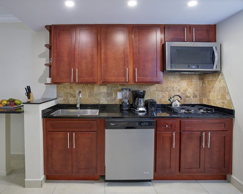 A well furnished living room with a television an open plan kitchen and dining area.