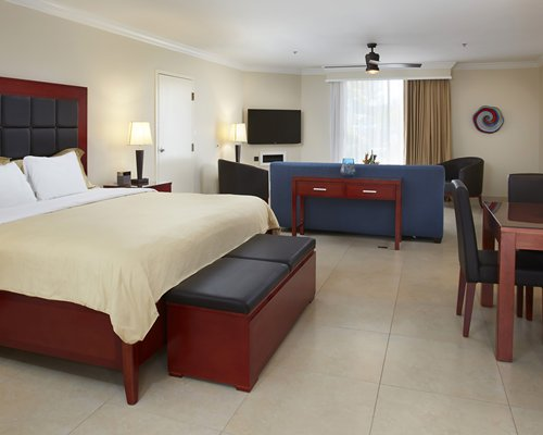 A well furnished bedroom with king bed television and a balcony view of the sea.