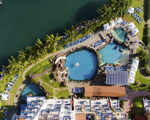 El Cid Marina Beach with an outdoor swimming pool grotto pool chaise lounge chairs and gazebos.