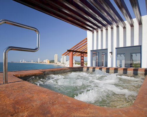 A hot tub alongside the resort units and the beach.