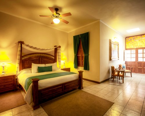 A well furnished large bedroom with two lamps and patio furniture.