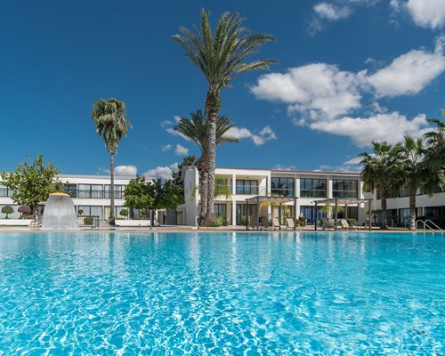 A large outdoor swimming pool with a raining mushroom umbrella alongside multi story resort units.