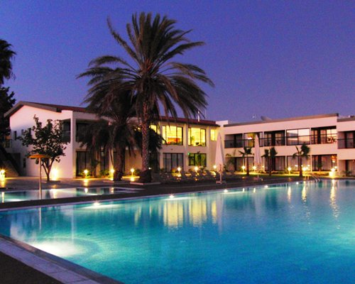 An outdoor swimming pool with chaise lounge chairs and sunshades alongside multi story resort units at dusk.