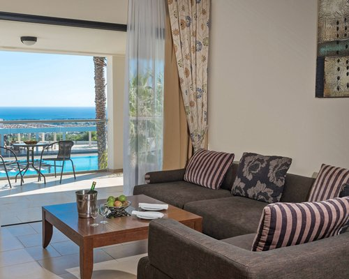 A well furnished living room with patio and outside view of the swimming pool.