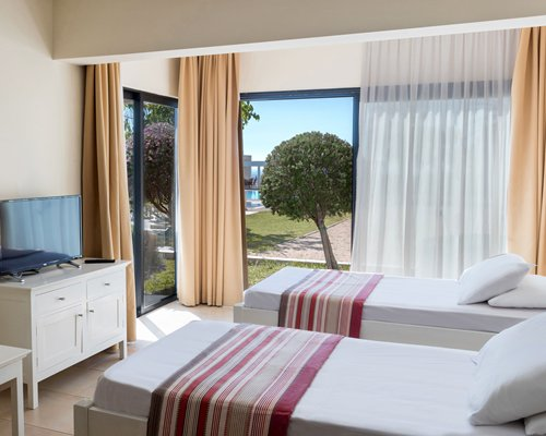 A well furnished bedroom with two twin beds a television and patio.