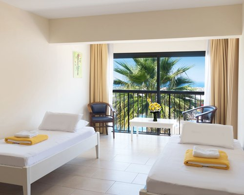 A well furnished bedroom with two twin beds and a balcony with patio.