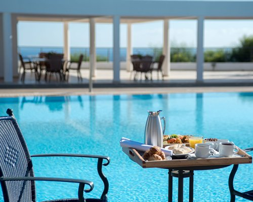 View of various foods placed on a table alongside the swimming pool.