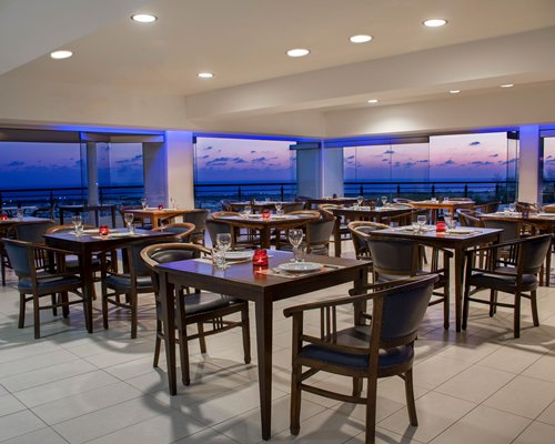 A well furnished indoor fine dining restaurant with an outside view.