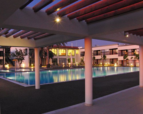 An outdoor swimming pool with chaise lounge chairs alongside resort units at dusk.