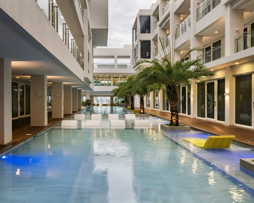A pool with chaise lounge chairs and palm trees alongside multi story resort units.