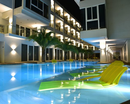 An outdoor swimming pool with in pool chaise lounge chairs alongside trees and multi story units.