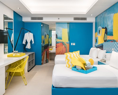 A well furnished bedroom with a television and two beds.