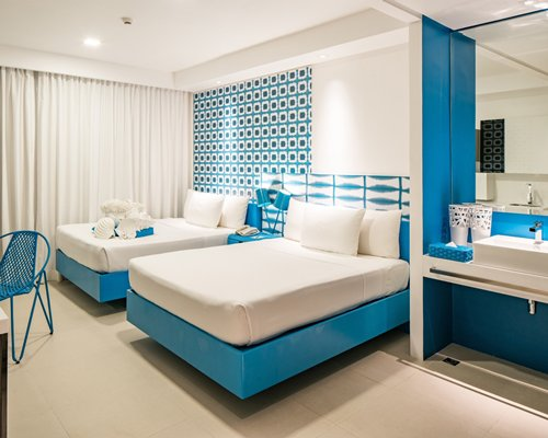 A well furnished bedroom with two twin beds and a sink.