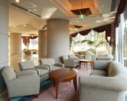 A well furnished large lounge area of the resort with an outside view.