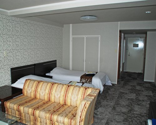 A well furnished bedroom with two twin beds and a sofa.