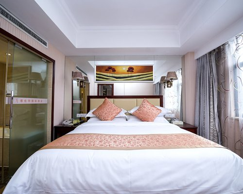 A well furnished bedroom with king bed and bathroom.