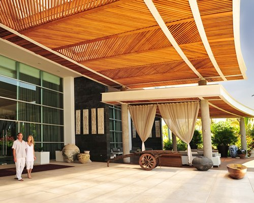 Scenic exterior view and a couple at the entrance of Grand Luxxe at Vidanta Nuevo Vallarta.