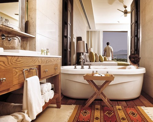 A man staining on the balcony of a well furnished bedroom and bathroom with an open sink vanity and bathtub.