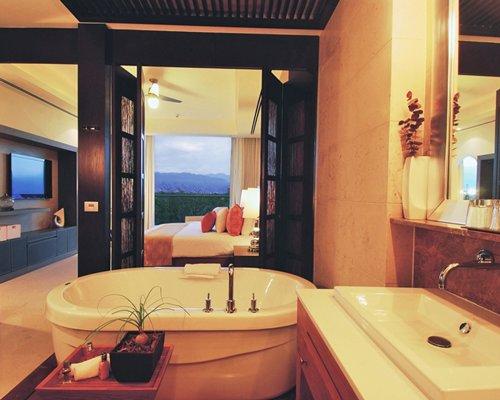 A bathtub and single sink vanity alongside a bedroom.