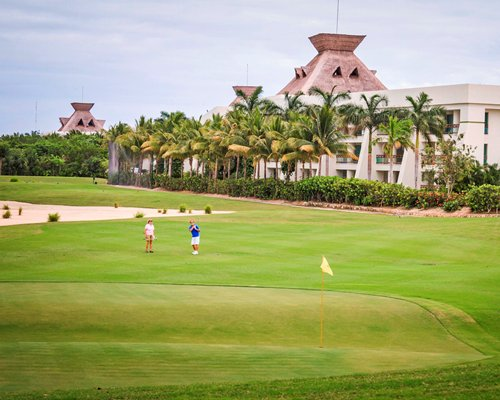 A well maintained golf course putting green alongside resort.