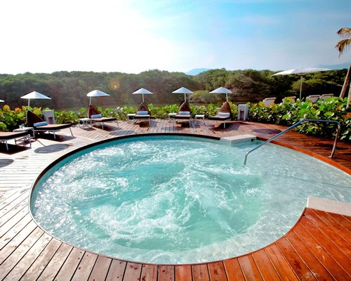 An outdoor hot tub with chaise lounge chairs and sunshades.