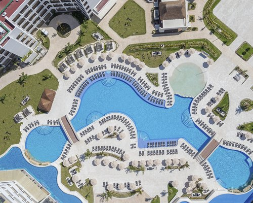 An Outdoor Swimming Pool With A Hot Tub And Chaise Lounge Chairs Alongside The Resort Unit