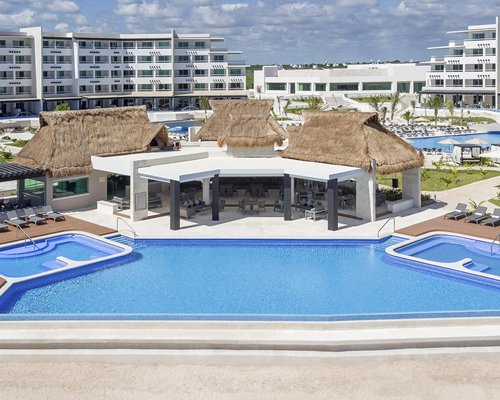 An outdoor swimming pool with chaise lounge chairs alongside the multi story resort unit.