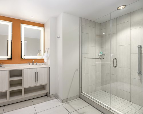 A bathroom with a standing shower stall and double sink vanity.